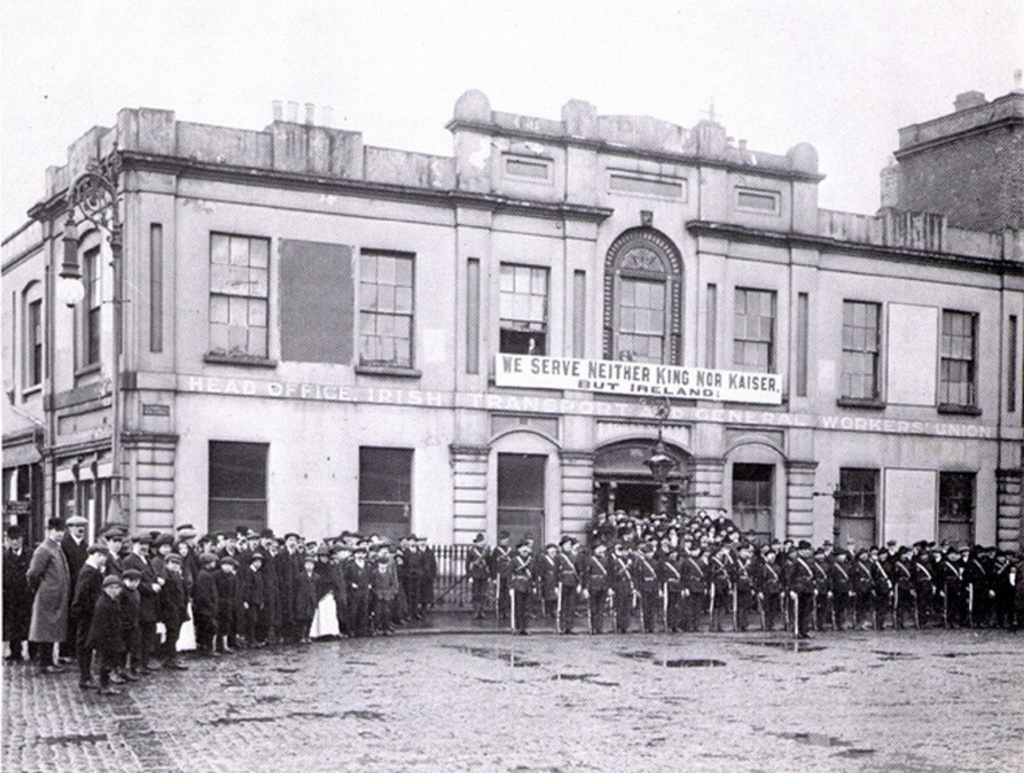 Irish Citizens Army in formation outside Liberty Hall. The banner reads 'we serve neither King nor Kaiser but Ireland'.