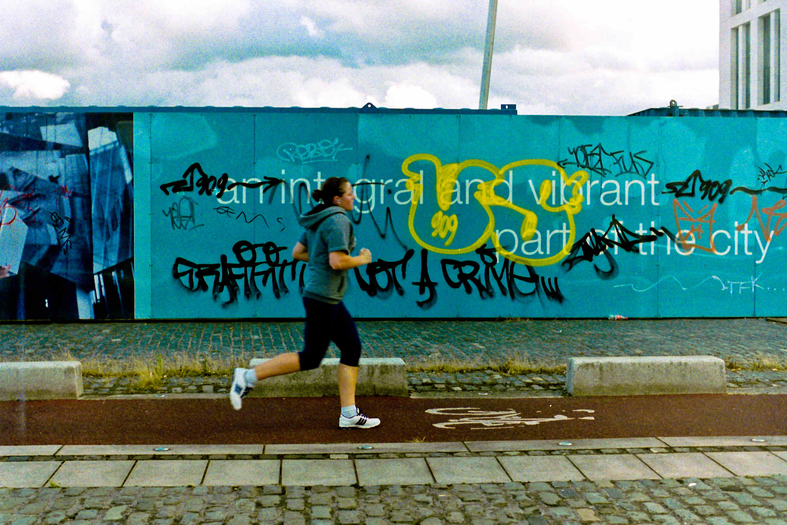 Woman running past hoarding with graffiti in Dublin docklands