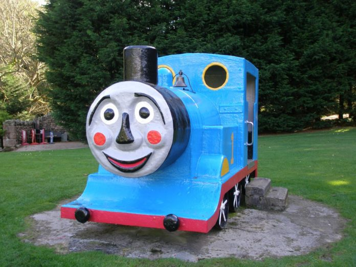 A photo of Thomas the Tank Engine in a playground with a terrifying face.