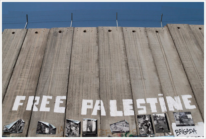 A photo of the immeasurably high apartheid wall with the words 'FREE PALESTINE' painted on it.