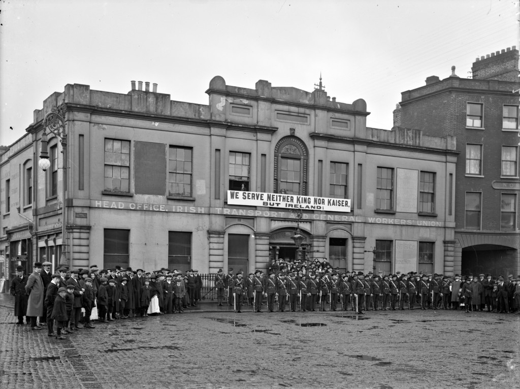 Irish Citizen Army group outside Liberty Hall. Group are lined up outside ITGWU HQ under a banner proclaiming