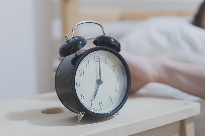 Photo of a black old style alarm clock and a hand leaning out of a bed to knock it off