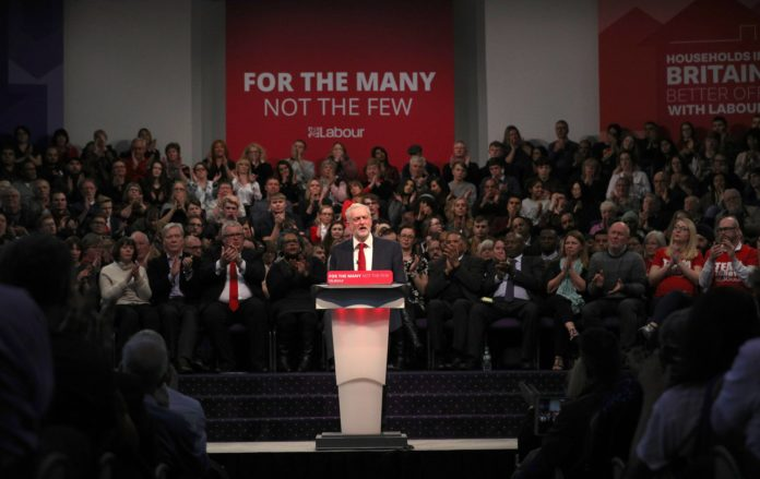 Jeremy Corbyn stands in front of a crowd at a conference with the sign behind reading 'For The Many, Not the Few'