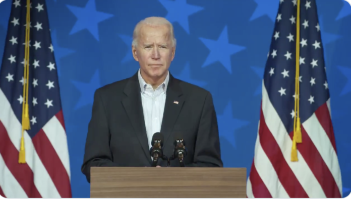 Joe Biden stands in front of two US flags