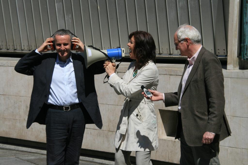 Green Party TD Ciaran Cuffe covers his ears as Senator Deirdre de Burca shouts through a megaphone and Environment Minister John Gormley measures the noise.