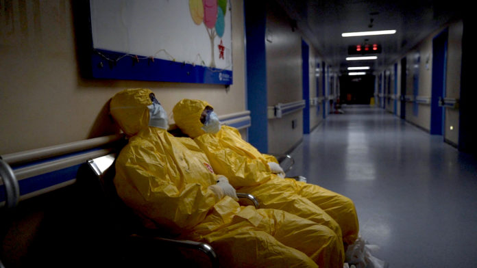 2 medical staff wearing yellow PPE and masks rest on chairs in a long hospital corridor.