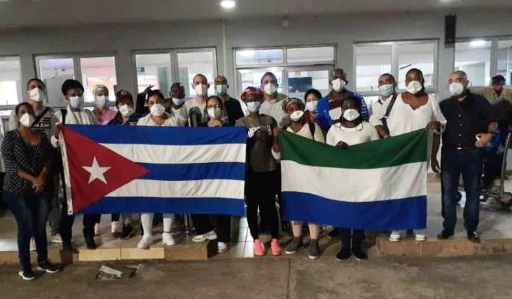 Groups of doctors in masks hold the Cuban national flag and the national flag of Sierra Leone.