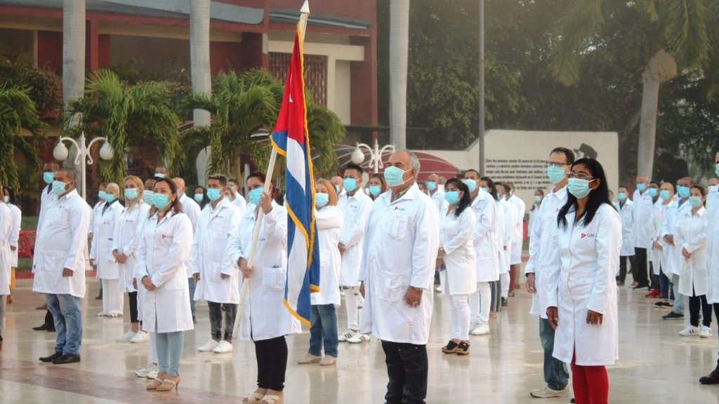 Many doctors stand in white coats and masks and one holds the Cuban national flag.