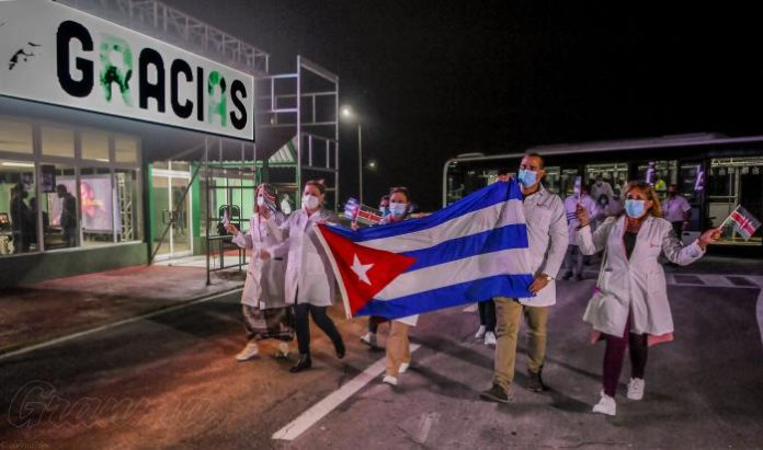 Doctors wearing white coats and masks walk along a road holding the Cuban national flag in front of a sign saying