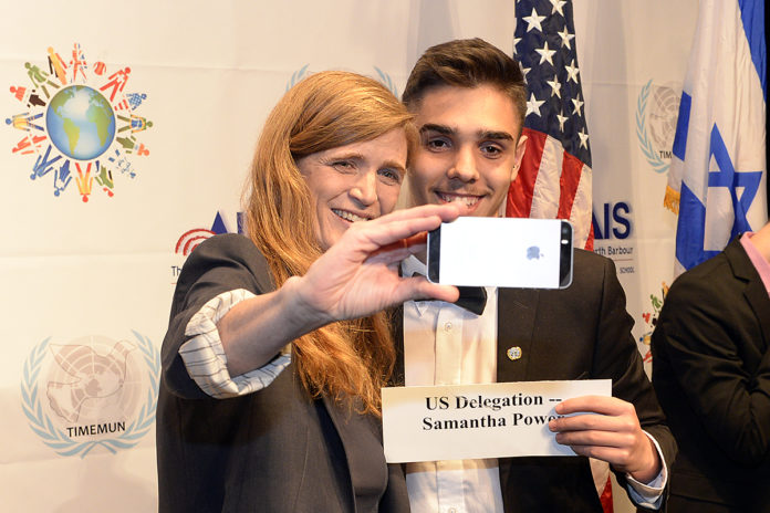 Samantha Power takes a selfie with a student who is holding a name tag that reads
