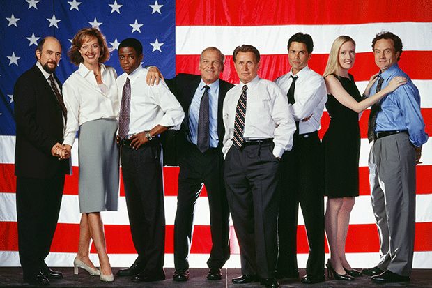 The cast of The West Wing stand in front of a US flag background.