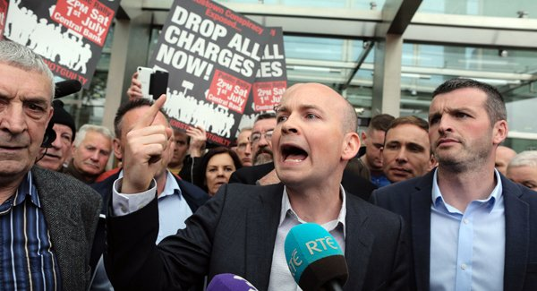 Paul Murphy makes a speech outside the court with a sign behind him reading 'Drop all charges now'