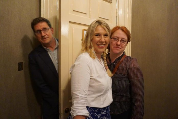 Eamon Ryan pops his head behind a door as Senator Alice Mary Higgins and another activist take a photo.