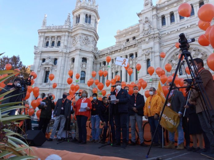 There is a platform in front of a fancy white building. Adults in masks holding orange balloons stand on the platform.