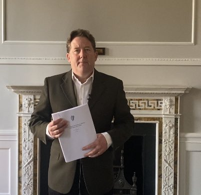 Darragh O'Brien holds a number of pages while standing in front of a fancy white fireplace
