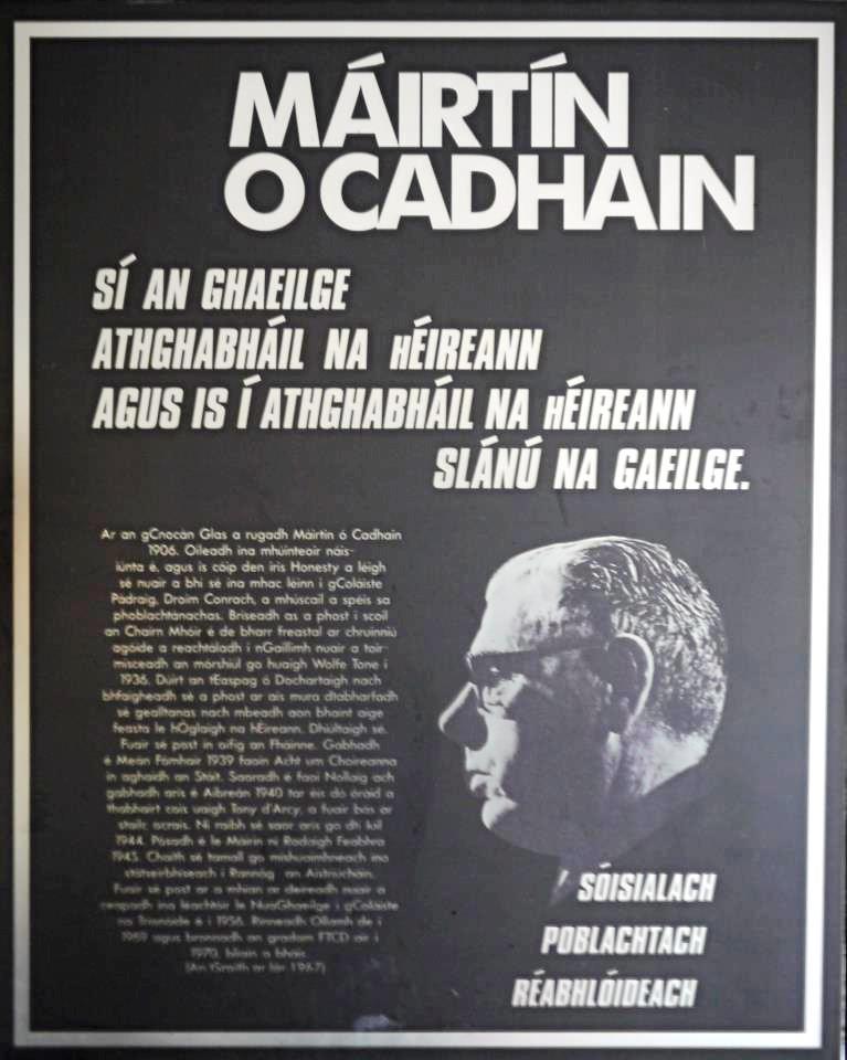 """A black poster with white writing which says """"Máirtín Ó Cadhain"""". Below it says """"Sí an Ghaeilge Athghabháil na hÉireann agus is í Athghabháil na Éireann Slánú na Gaeilge"""". Over an image of Ó Cadhain are the words """"Sóisialach, Poblachtach, Réabhlóideach""""."""