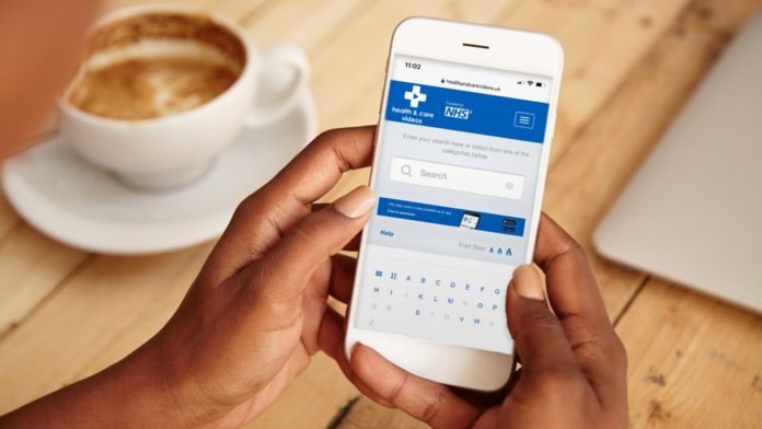A phone open on the NHS app is held in two hands while a cup of coffee is in the background.