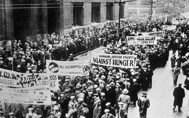 An old black and white photo of a busy protest going down a street