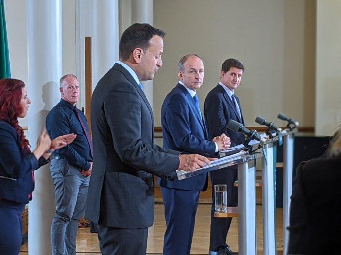 Leo Varadkar, Michael Martin and Eamon Ryan stand at lecterns while ISL translates stand behind.
