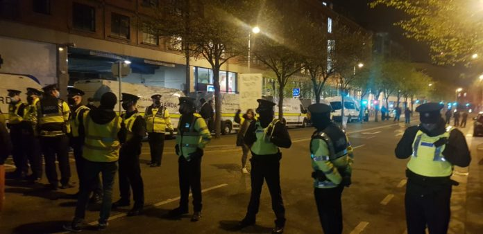 At night a line of Gardaí in high viz and Covid masks form a line across a street. There are lines of Garda vans in the background and a blurry image of a protester holding a placard.