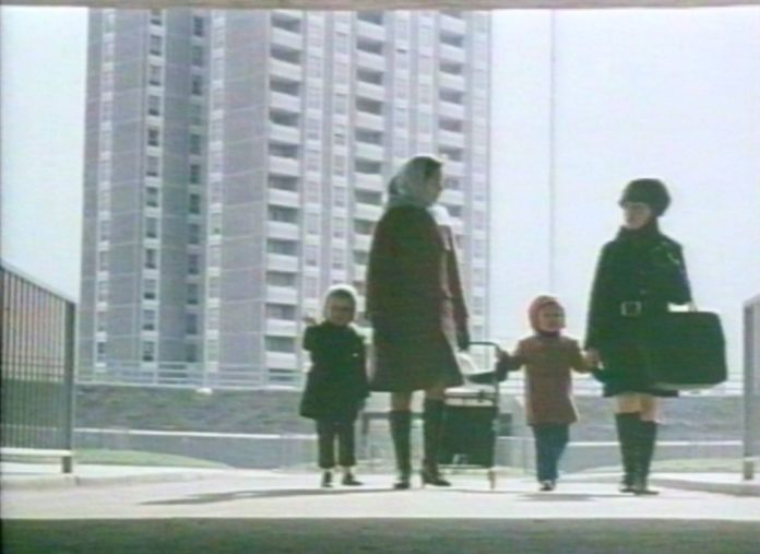 A still from a video shows two young women and their children walking in front of the Ballymun flats when they were new
