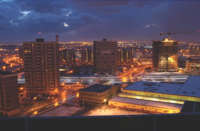 The Ballymun towers at night with Dublin City stretching out behind.