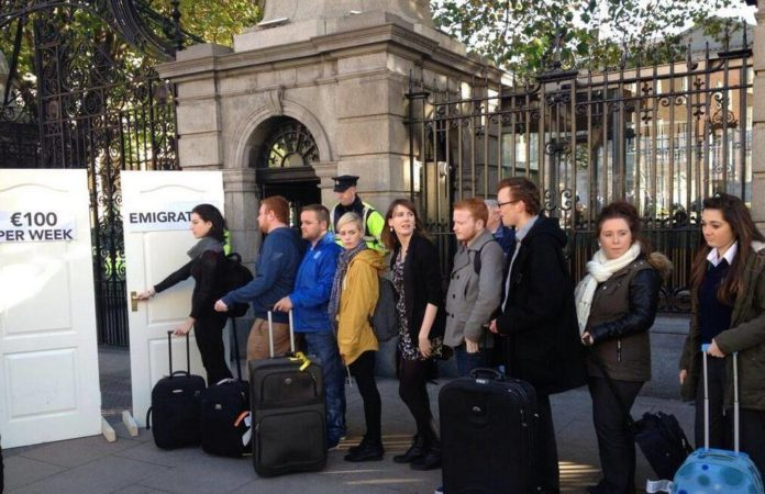 A number of young people queue in front of Leinster House with suitcases. They can choose between two doors, one of which says