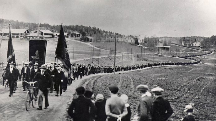 A black and white photo of what looks like a long procession led by trade union banners making its way through the countryside.