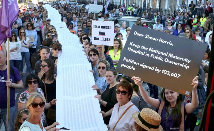 A packed street at a demo as people hold a long line of signatures