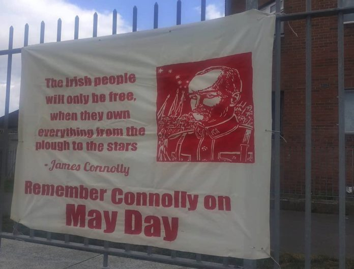 A white banner hangs up on a fence. It is hand painted in red. There is a picture of James Connolly and the words