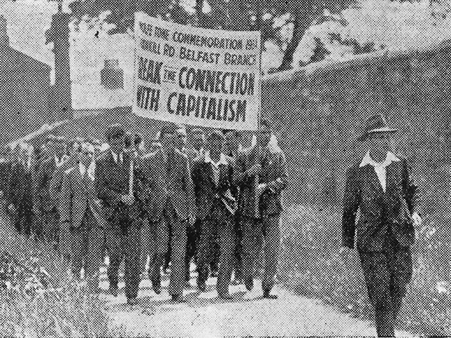 An old black and white photo shows rows of men walking down a path holding a banner which reads