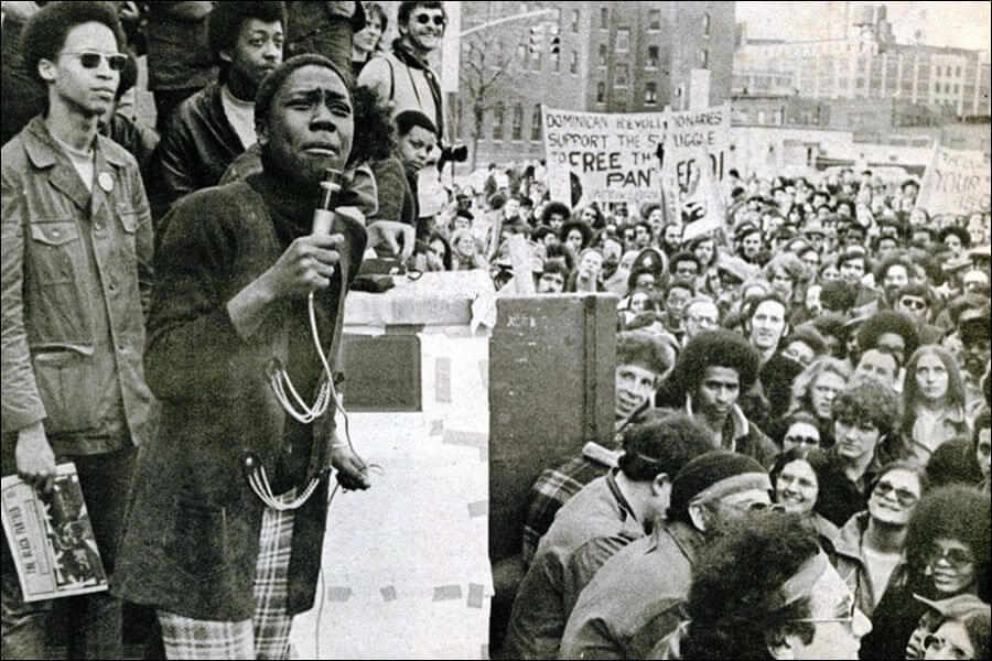 A black and white photo of a young Afeni Shakur speaking into a megaphone on a platform above a large crowd.