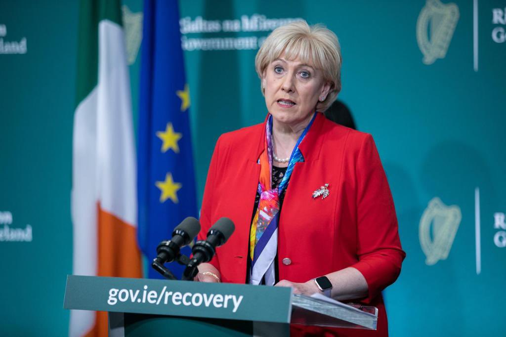 Minister Heather Humphreys speaks at a podium which says gov.ie/recovery and in front of the Irish and EU flags