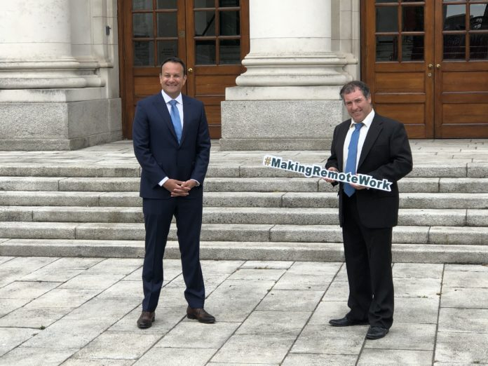 Leo Varadkar stands in front of Government Buildings while another man holds a sign saying #MakingRemoteWork