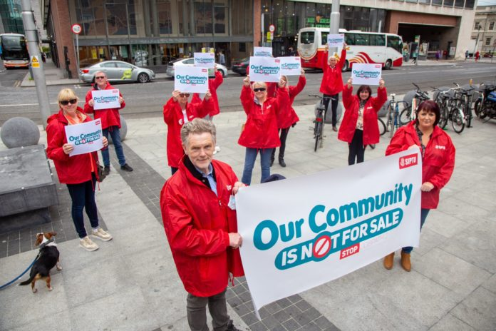 Several SIPTU members in red coats hold up banners and placards reading