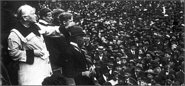 A black and white photo of Clara Zetkin in the left foreground looking over a crowd