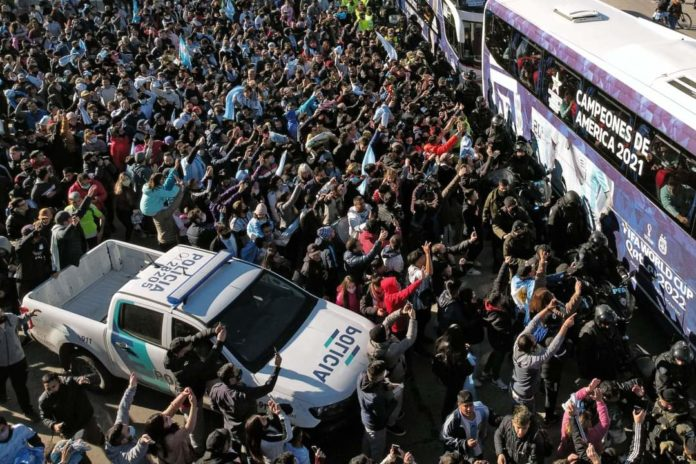 An image of a huge crowd gathering around the Argentinian football team's bus